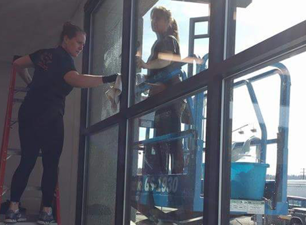 Professional housekeepers washing inside and outside windows